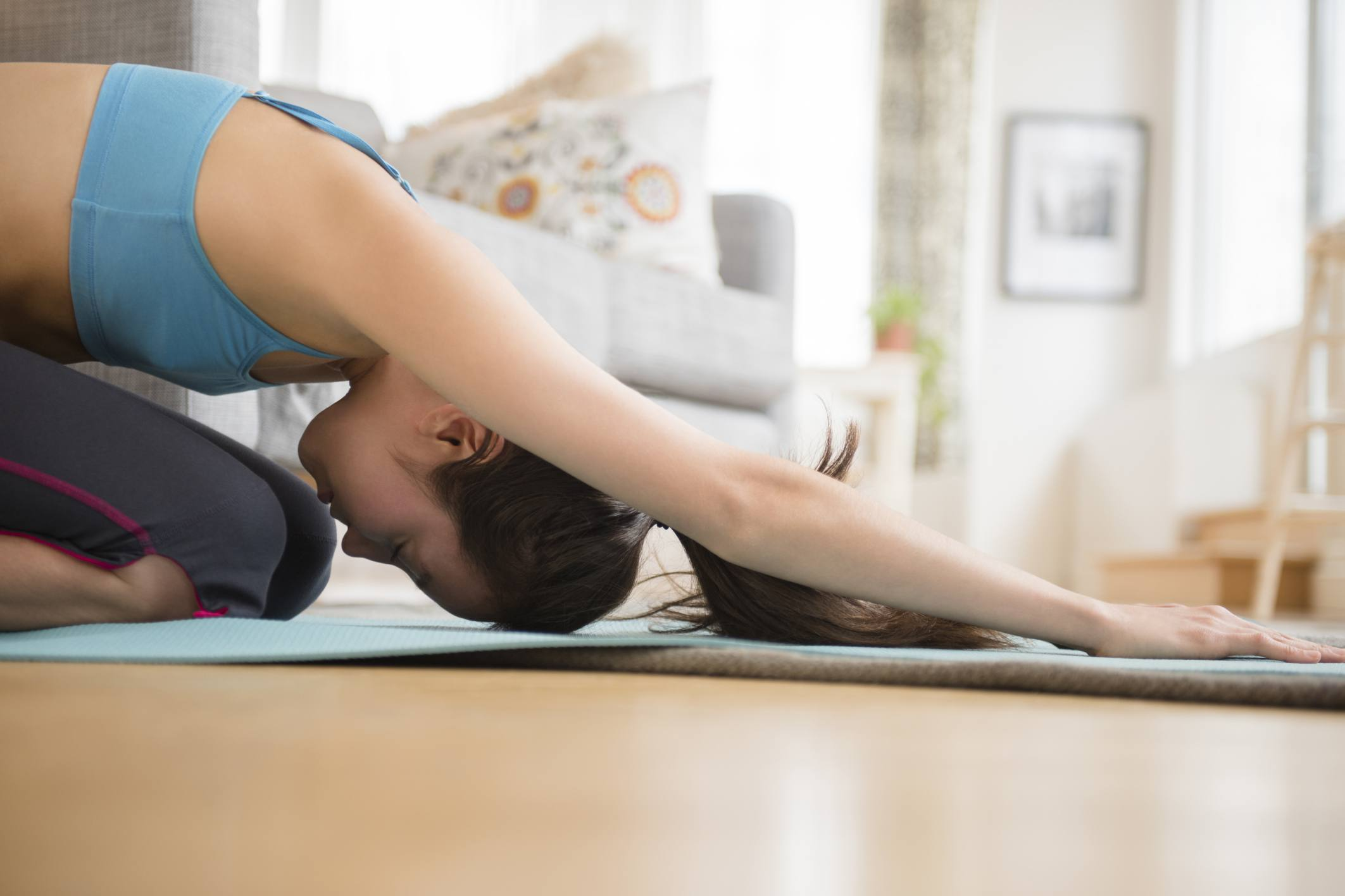 Mujer estirando sobre colchoneta de ejercicios en casa