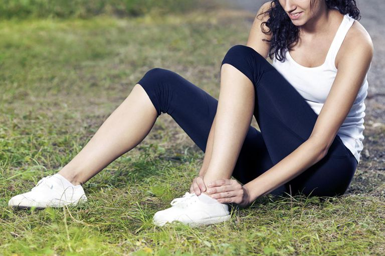 Young woman feeling pain in the ankle