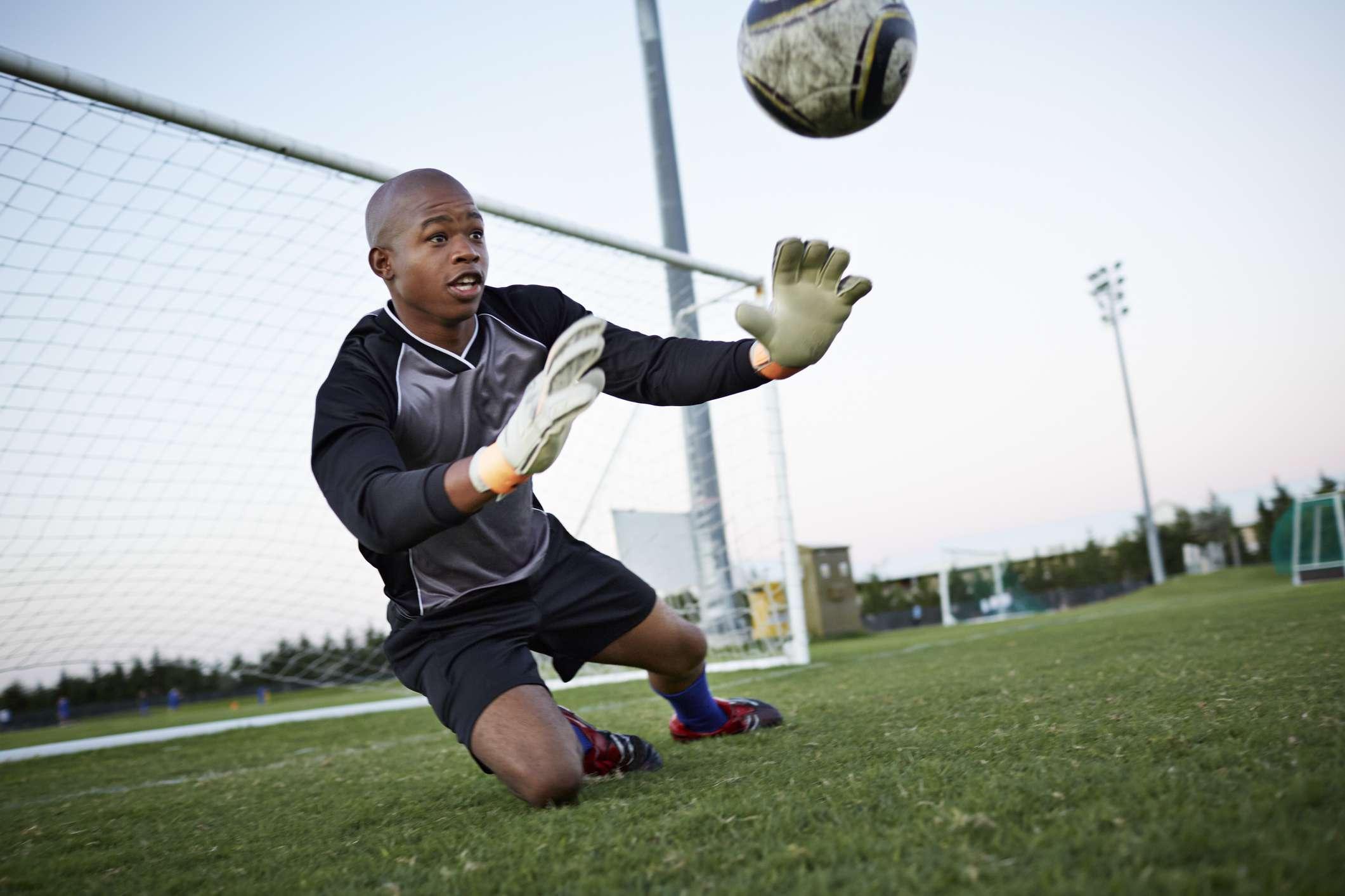 Portero saltando para atrapar el fútbol