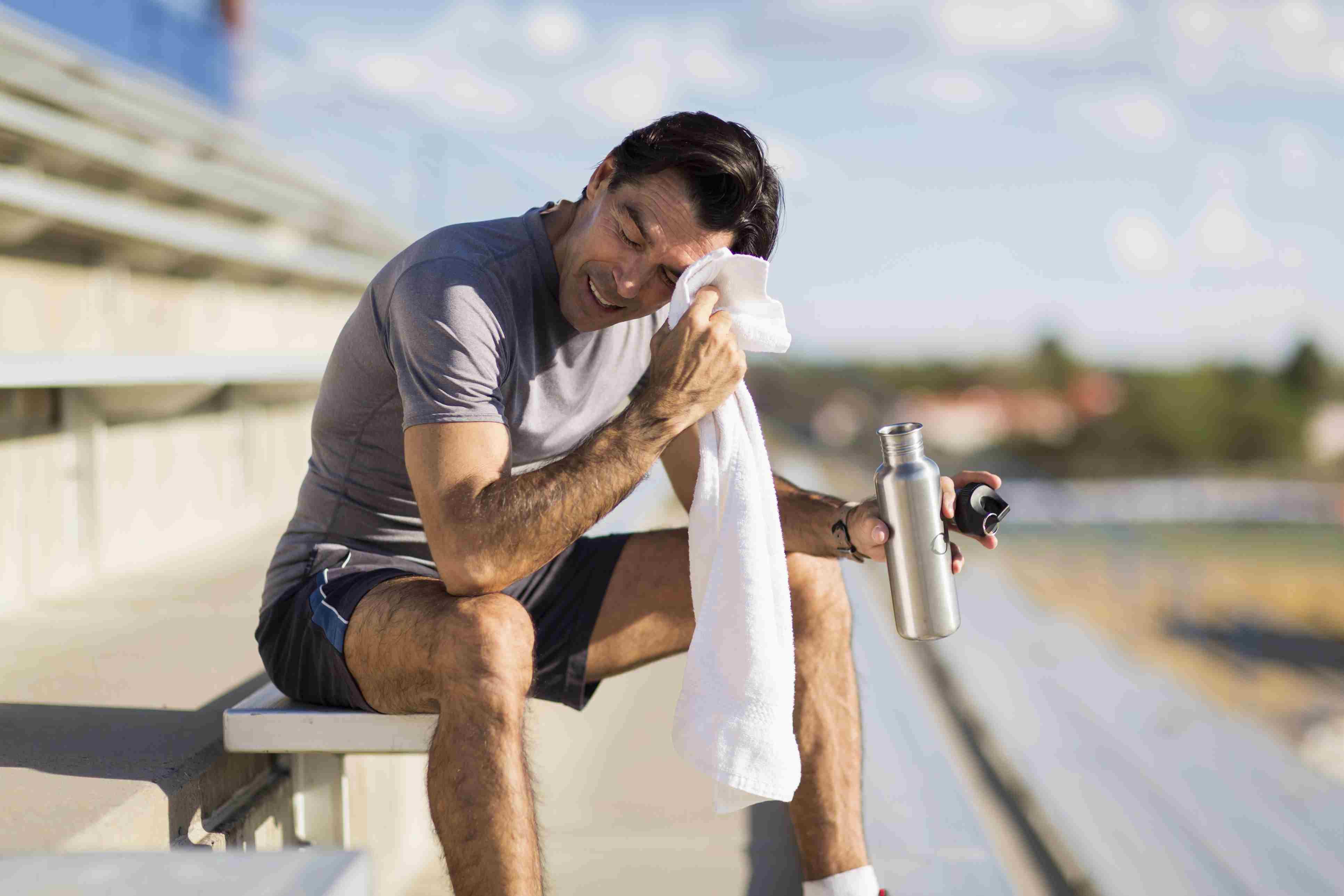 Sweaty man resting on bleachers.
