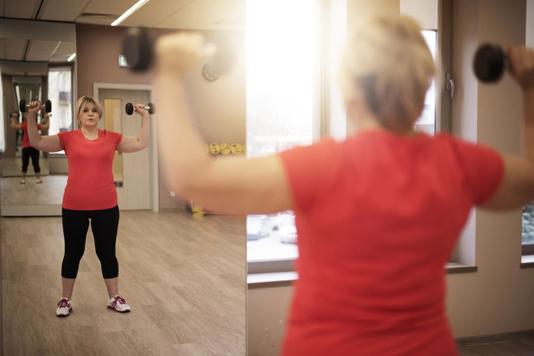 overweight woman lifting dumbbells in gym