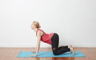 woman doing cat cow pose