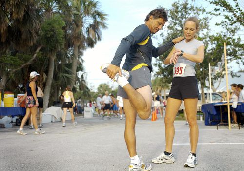 Hombre estirando junto a una mujer antes de una media maratón