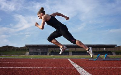 Woman taking off running on a track