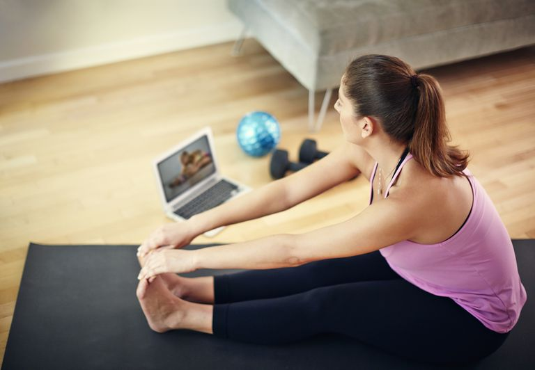 Woman doing stretches in front of laptop