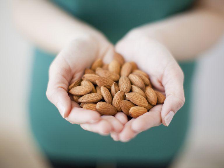 Studio shot of woman showing handful of almonds