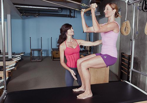 A female exerciser and an instructor doing pilates