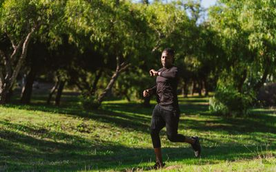 man running in park checking fitness watch