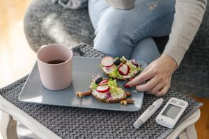 Young woman wearing grey cotton top and light-blue jeans with a rip at the thigh. She has burgundy nails, and is reaching for an olive on a grey trey containing two slices of wheat bread which have lettuce and cashew nuts on them. A pink coffee mug containing half-empty coffee is on the tray. A blood sugar monitor and an insulin pen are next to the tray. They are placed on a grey table mat.