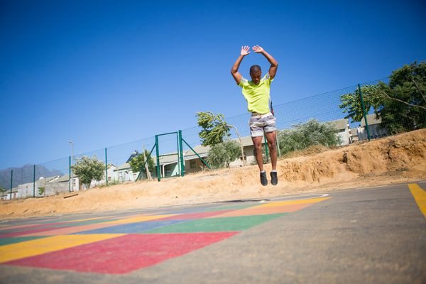 A young man performing aerobic exercise outdoors at a playground.