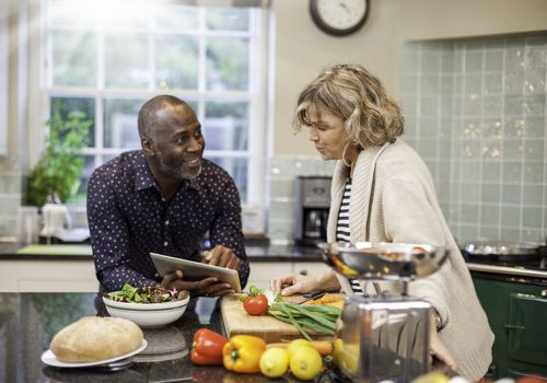 Multi-ethnic mature couple preparing food