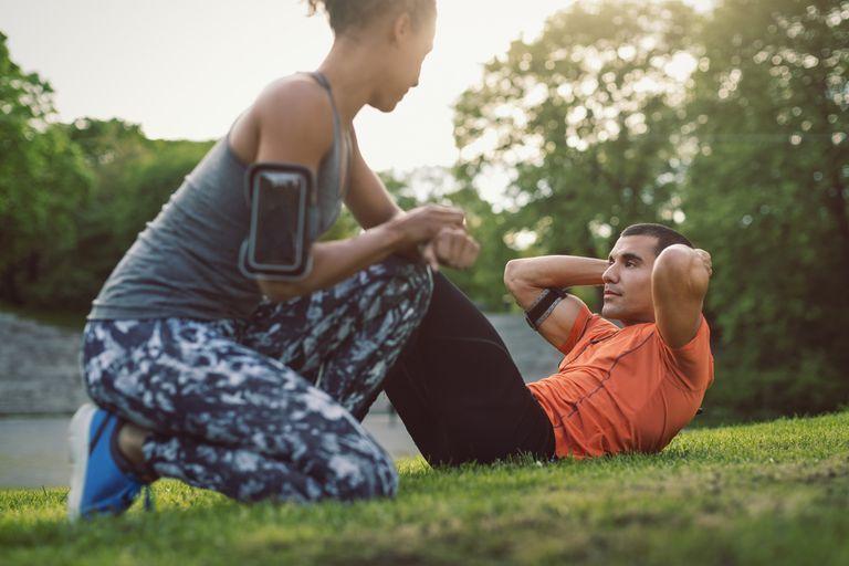 Woman kneeling and looking at man doing sit-ups at park
