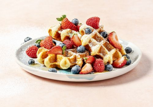 A plate of waffles with berries on peach background - stock photo