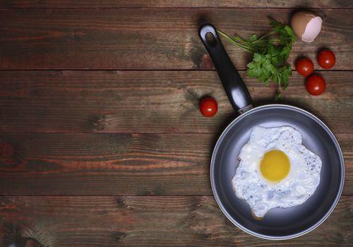 Sartén de huevo frito, con tomates cherry y perejil.