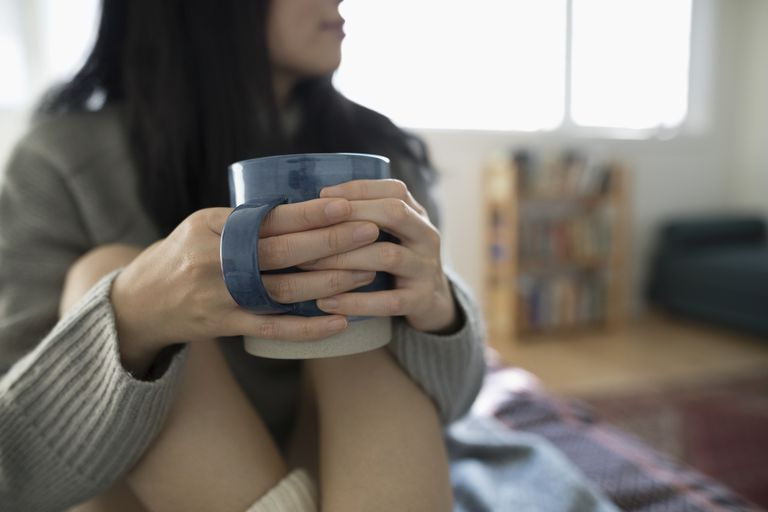 Close up woman drinking coffee on bed