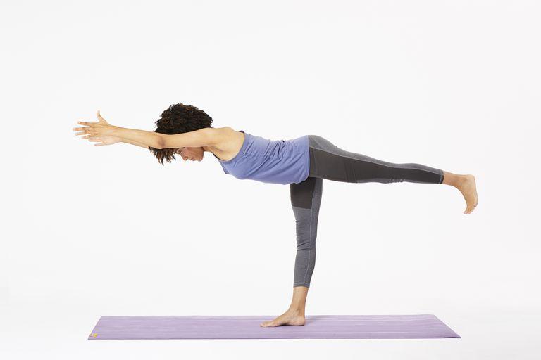Woman on yoga mat doing warrior III pose
