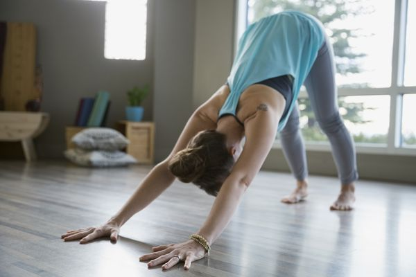 A woman does a yoga down dog pose with good form.