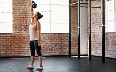 woman raising kettlebell over her head in an empty gym