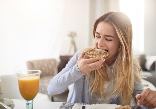 Chica de pelo rubio comiendo bagel de trigo y bebiendo jugo de naranja para el desayuno