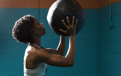 Side view of woman holding medicine ball while listening music against wall in gym