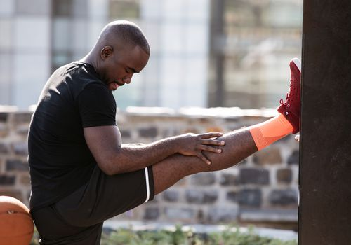 A man props his foot against a wall to stretch his hamstring in preparation for exercise.