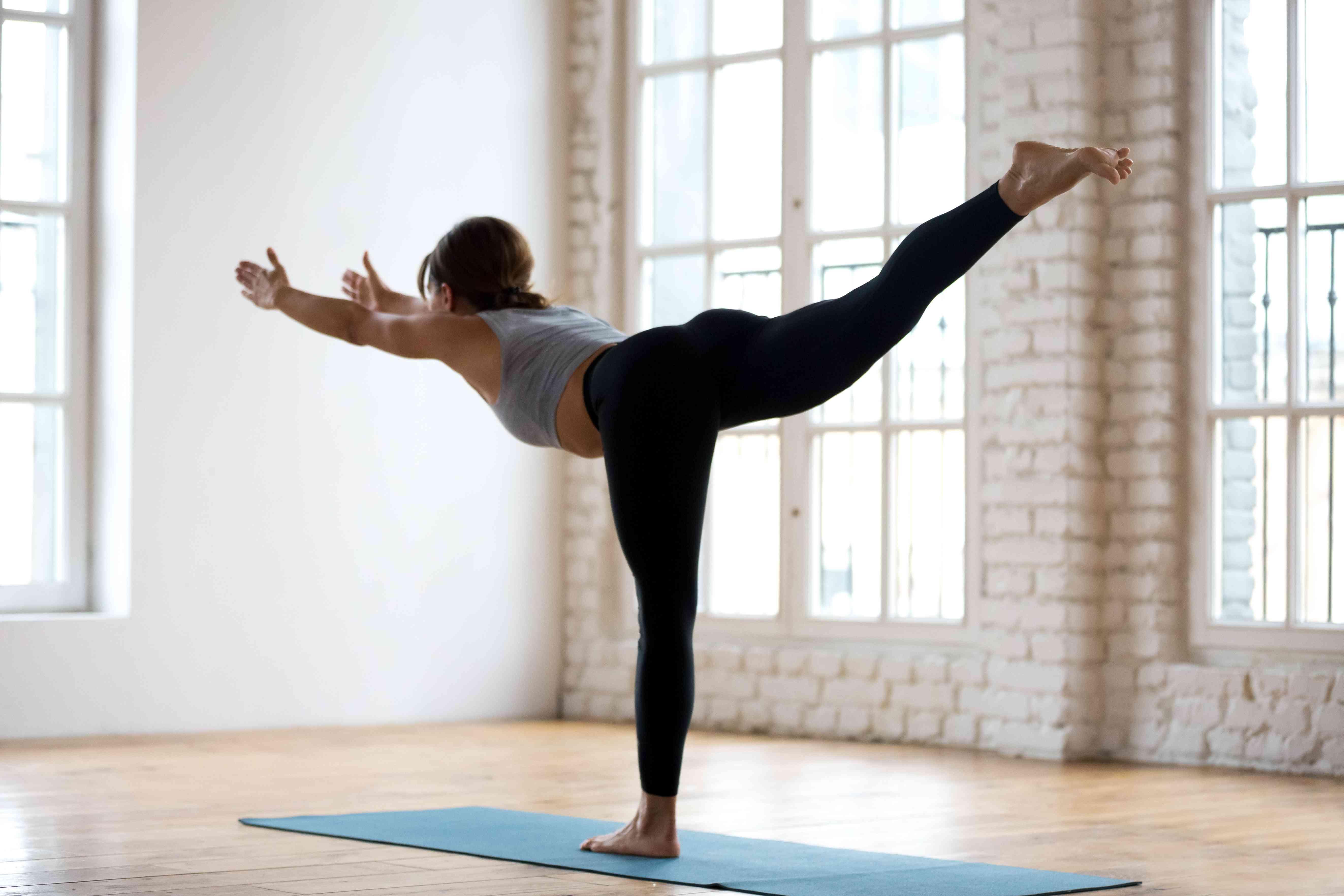 Joven atractiva mujer deportiva practicando yoga, pose de Guerrero tres