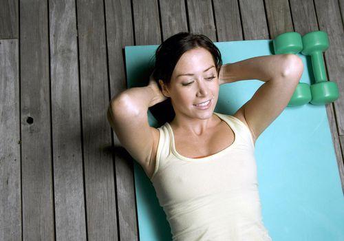 Mujer joven, mentira en estera del ejercicio, con, manos detrás de la cabeza, sonriente