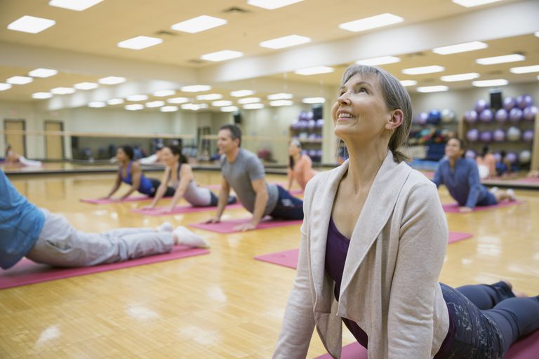 A group of people taking a yoga class at a gym