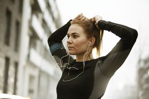 woman wearing headphones tightening ponytail on city street