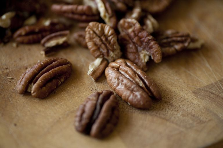 Freshly roasted organic pecans sit on a wooden cutting board in a kitchen in Seattle, Washington.
