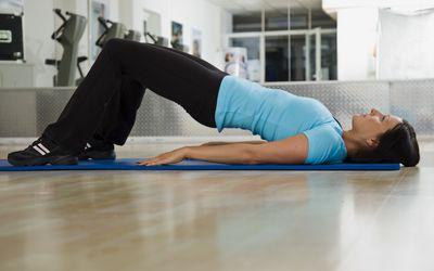 a woman doing a bridge exercise on a mat