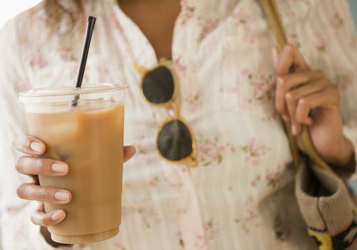 A woman holds a cup of iced coffee with a straw.