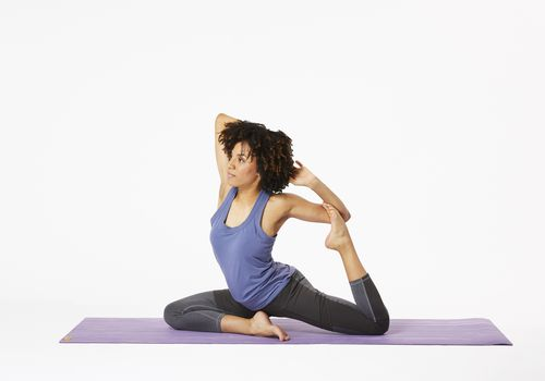 Woman sitting on yoga mat in mermaid pose