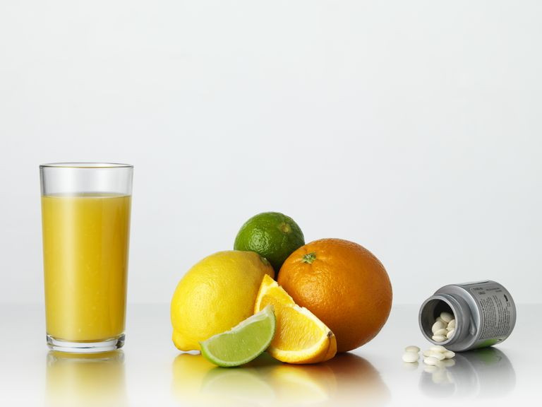 Glass of juice, citrus fruits and vitamin tablets