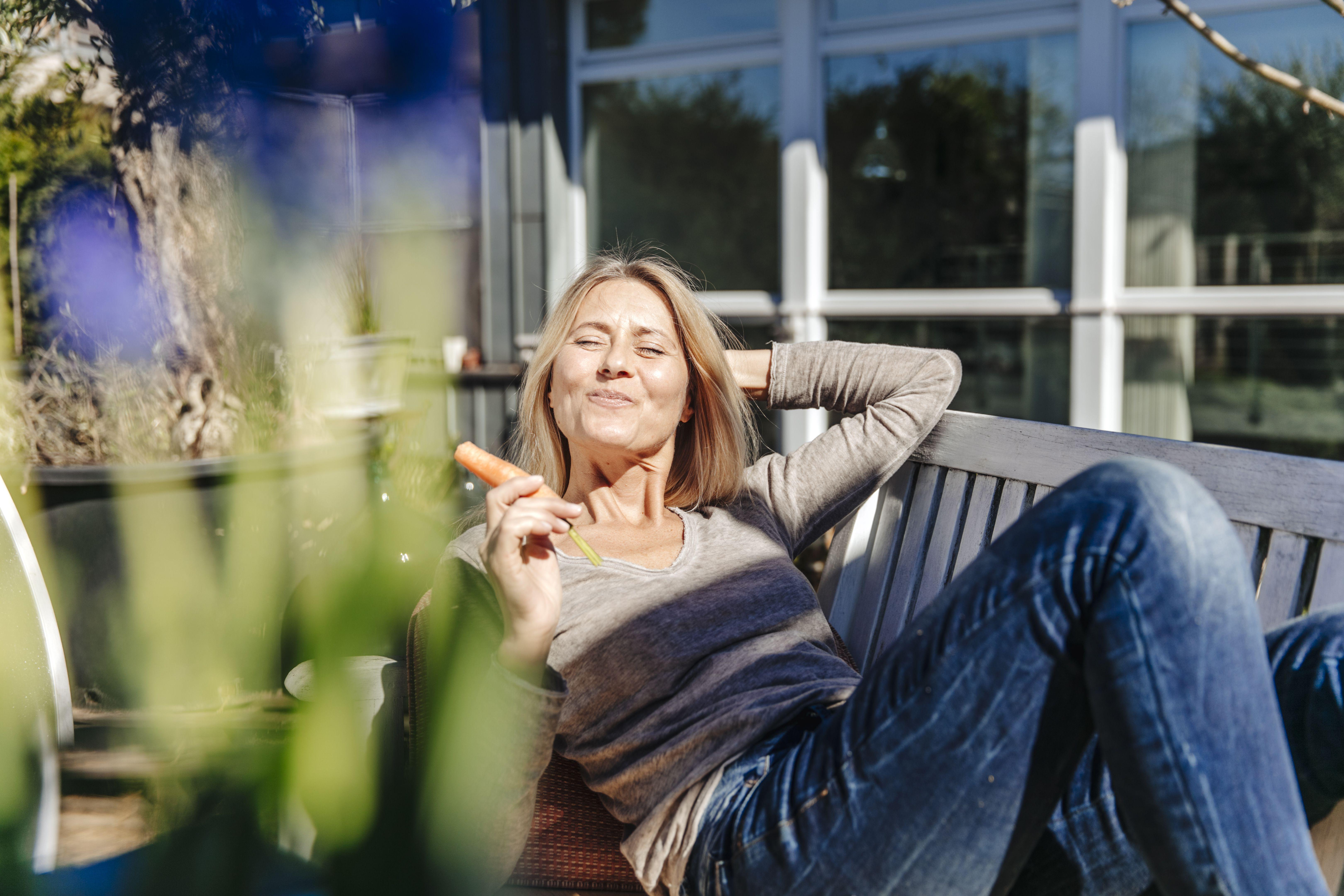 Mujer descansando en un banco del jardín comiendo una zanahoria