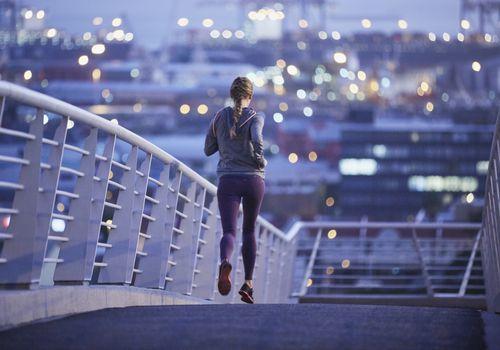 Corredor femenino corriendo en la pasarela urbana al amanecer