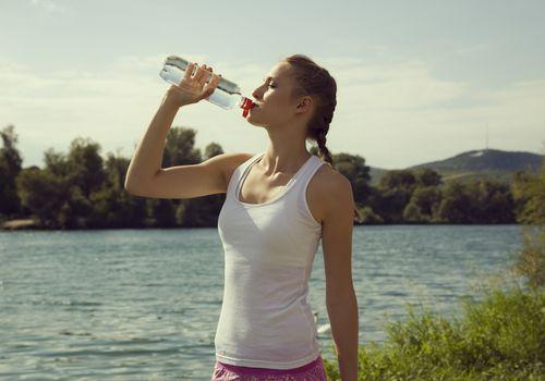 Mujer bebiendo agua de botella de agua