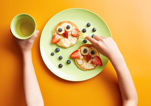 Child eating pancakes and fruit