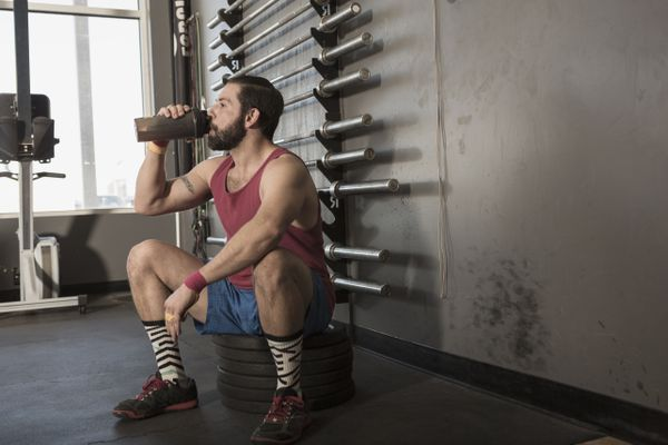 Mixed Race man drinking from bottle in gymnasium
