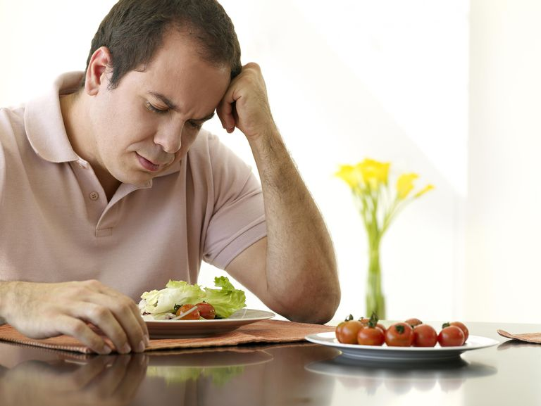 Sad man eating a salad