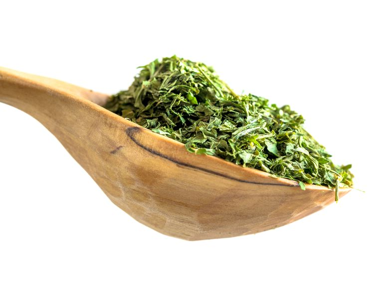 Parsley flakes condiment or spice in a wooden rustic spoon over a white background