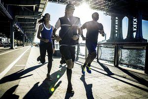 Team running together on bridge, New York, USA