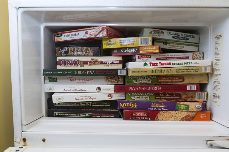 Home Freezer Compartment Packed with Frozen Pizza Boxes