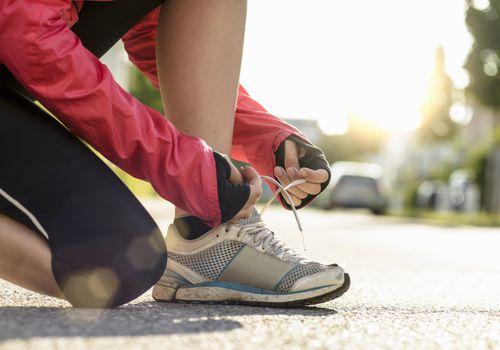 Corredor femenino atar cordones de zapatos en una zona urbana