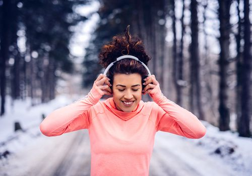 a woman running while listening to music via headphones on a snowy, tree-lined road