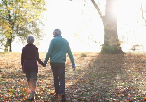 elderly couple walking in park.