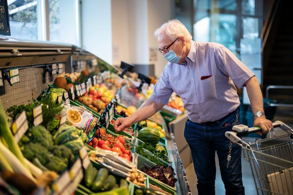 Image of elderly man with a mask leaning over the produce section in a market.