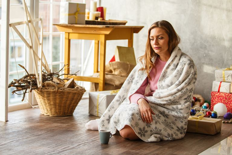 Young woman wrapped in a blanket is sitting on floor and looking sick.