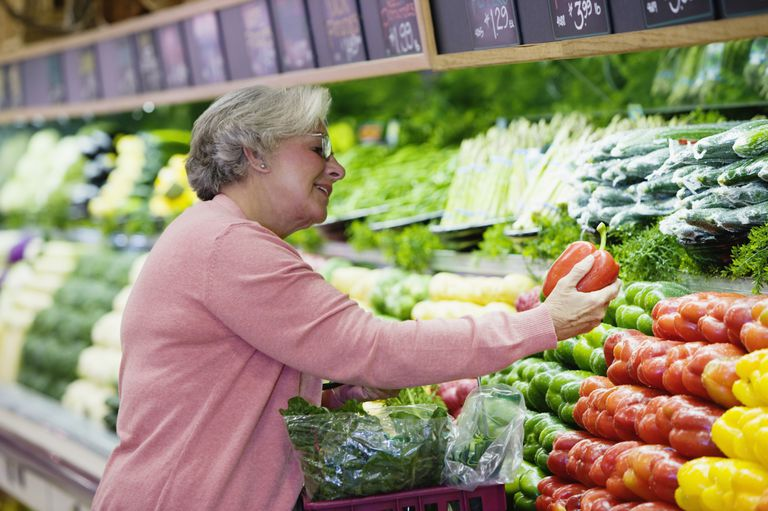 Woman looking at peppers in grocery store, smiling