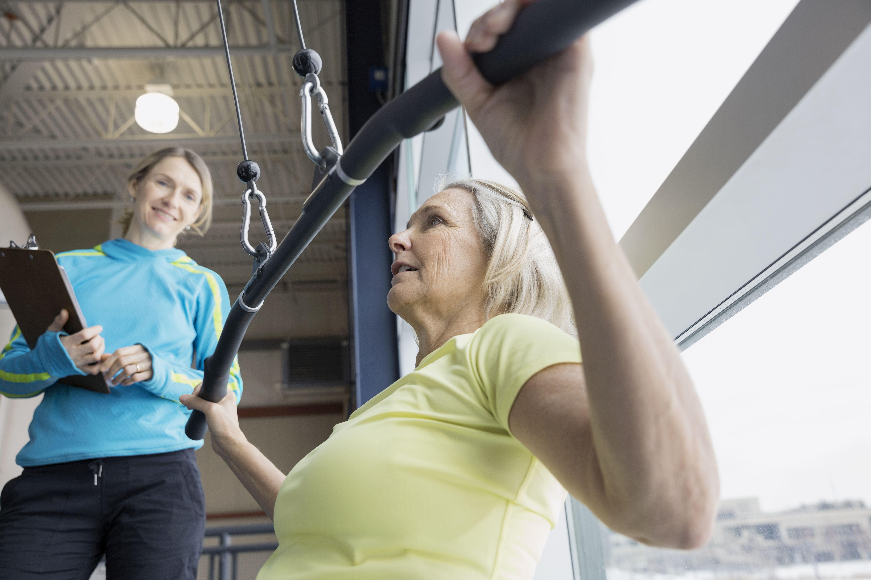 Entrenador mujer guía en máquina de pesas